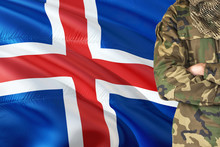 Crossed Arms Soldier With National Waving Flag On Background - Iceland Military Theme.
