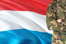 Crossed Arms Soldier With National Waving Flag On Background - Luxembourg Military Theme.