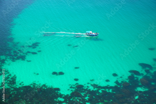 Foto auf AluDibond Reef grun Boat on transparent sea surface.
