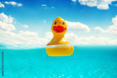 Valokuva  Rubber duckling floating in water. Summer vacation.