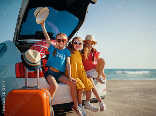 plakat happy children girls friends sisters on the car ride to summer trip.