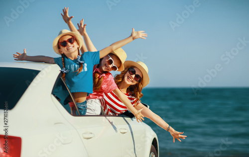 fototapeta na lodówkę happy family mother and children girls goes to summer travel trip in car.