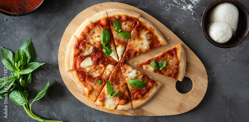 Photo sur Aluminium Pizzeria Top view of Pizza Margherita on black stone background. Classic Italian Pizza Margarita with Tomato sause, Basil and Mozzarella Cheese background.
