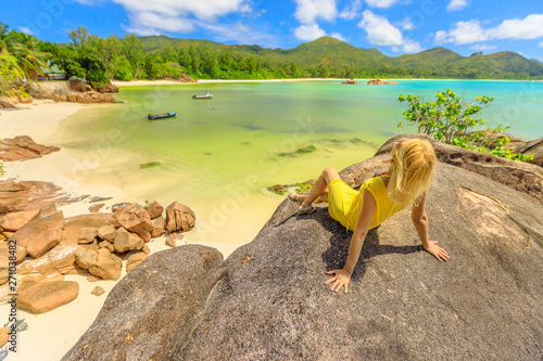 Foto auf Gartenposter Gelb Schwefelsäure Caucasian lifestyle tourist woman in yellow sunbathing on granite boulder at Anse Gouvernement with crystal waters and pristine beach near Cote d'Or Bay. Scenic landscape of Praslin in Seychelles.