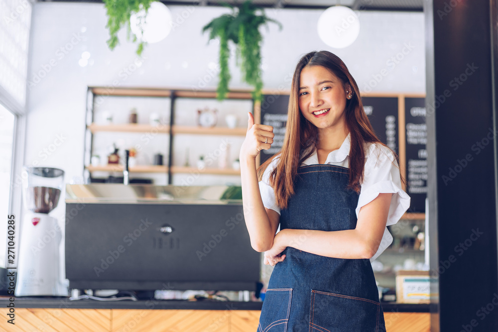 Fototapeta Pretty young asian waitress standing arms crossed in cafeteria.Coffee Business owner Concept.  barista in apron smiling at camera in coffee shop counter