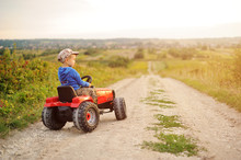 Child With A Toy Tractor On A Trip.