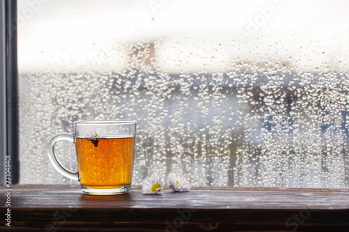 Foto cup of tea  on  background of  window with raindrops at sunset