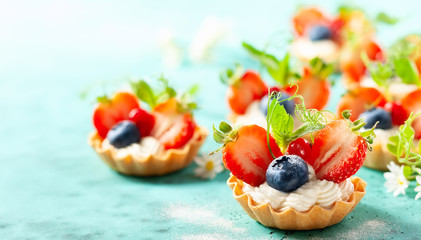 Summer berry tartlets with cream and fresh berries.