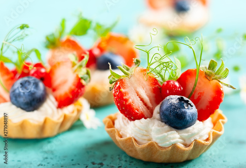 La pose en embrasure Fleur Summer berry tartlets with cream and fresh berries.