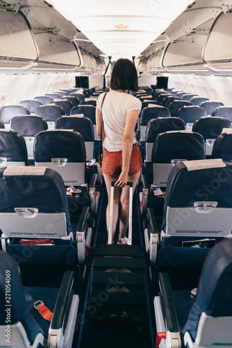 Fotomural Back view of young woman walking the aisle on plane