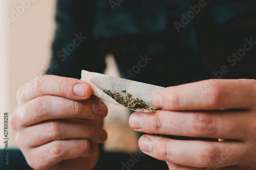 Photo  Man rolling a marijuana joint