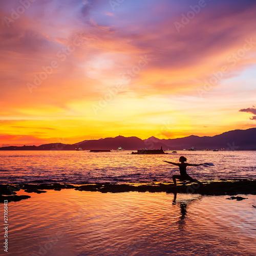 Valokuva  Caucasian woman practicing yoga at seashore
