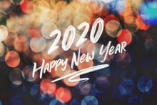 Brush Stroke Handwriting 2020 Happy New Year On Abstract Festive Colorful Bokeh Light Background,holiday Greeting Card.