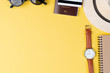 Top view travel concept with accessories on yellow background