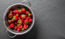Fresh Juicy Red Strawberries In Stainless Steel Colander On Dark Grey Black Slate Background