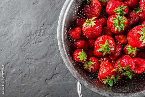Fotografía  Fresh juicy red strawberries in stainless steel colander on Dark grey black slat