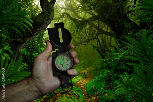 fototapeta na lodówkę Hand with compass in the jungle