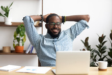 Smiling Afro-American Businessman Holding Hands Behind Head Sitting At Office