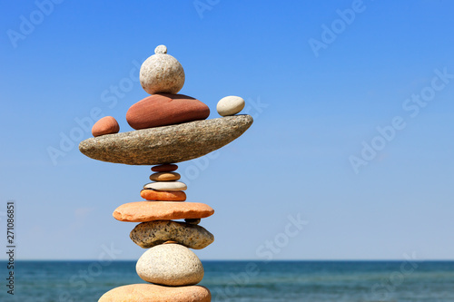 Poster de jardin Spa Rock zen pyramid of colorful pebbles on a beach on the background of the sea.