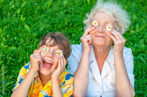 Obraz Happy grandmother and laughing   grandchild fooling around the law of putting chamomiles instead of eyes. Family love and relationships. Family happy holiday. - fototapety do salonu