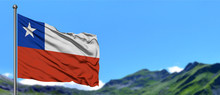 Chile Flag Waving In The Blue Sky With Green Fields At Mountain Peak Background. Nature Theme.