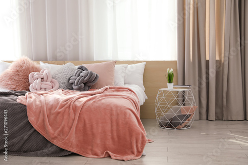 Foto Comfortable bed with pillows and plaid in modern room interior