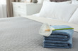 canvas print picture Stack of clean towels with flower on bed indoors. Space for text