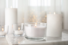 Burning Aromatic Candles In Holders On Table