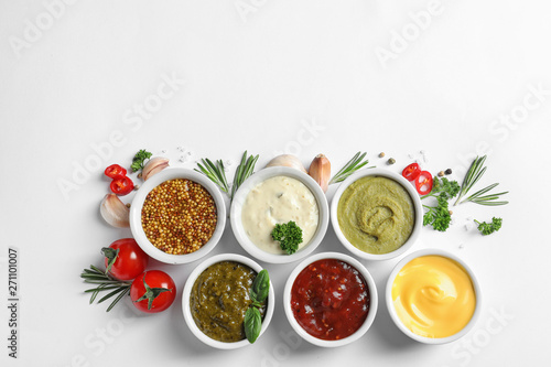 Photo  Composition with different sauces and ingredients on white background, flat lay
