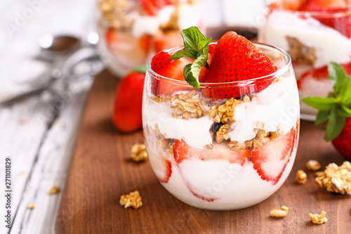 Fototapeta Healthy breakfast of strawberry parfaits made with fresh fruit, yogurt and granola over a rustic white table. Shallow depth of field with selective focus on glass jar in front. Blurred background. obraz