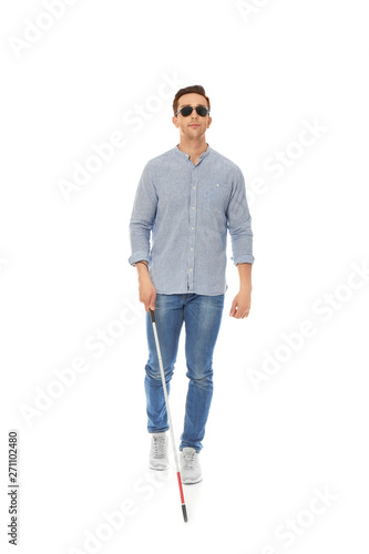 Young blind person with long cane walking on white background Fototapet