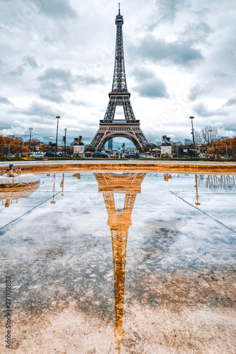 Paris Eiffel Tower and reflection on a rainy day in Paris, France. Eiffel Tower is one of the most iconic landmarks of Paris.