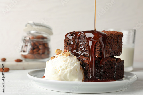 Pouring sauce onto fresh brownies served with ice-cream on plate, space for text. Delicious chocolate pie