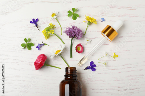 Bottle of essential oil and different flowers on white wooden background, flat lay - 271103093