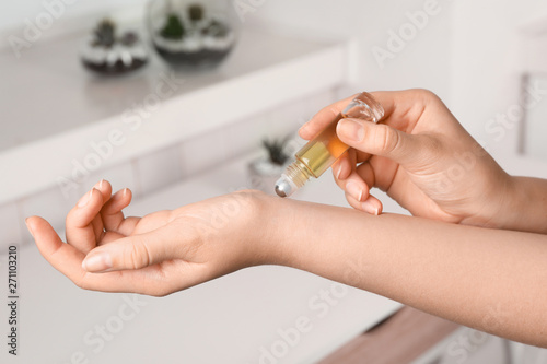 Photo Woman applying essential oil on wrist indoors, closeup