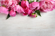 Leinwandbild Motiv Fragrant peonies on wooden table, top view with space for text. Beautiful spring flowers