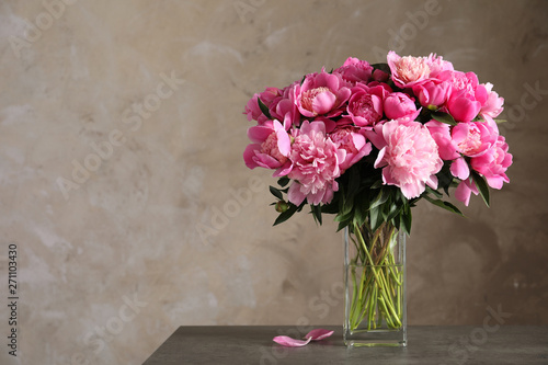 Fotografie, Tablou Fragrant peonies in vase on table against color background, space for text