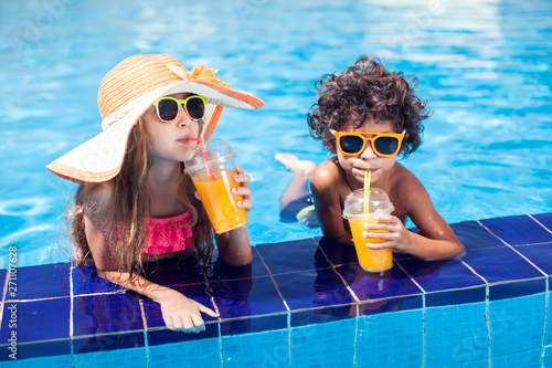 Two kids girl and boy drink juice in the pool and have fun. Children and summer concept