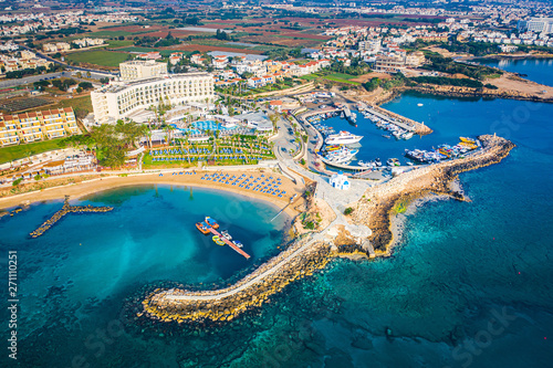 Cyprus. Protaras. The Paralimni harbour. Pernera. Kalamies beach top view. The jutting out into the sea beach forms the bays. St. Nicolas church Cyprus. Beach resort of Cyprus. Panorama with drone. - 271110251