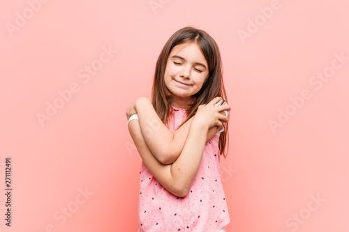 Photo  Cute little girl hugs himself, smiling carefree and happy.