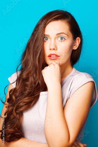young pretty teenage modern girl posing emotional happy on blue background, lifestyle people concept