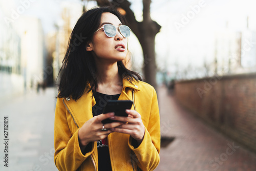 Valokuva  Half length portrait of thoughtful asian woman in trendy sunglasses enjoying smartphone chatting with close friends