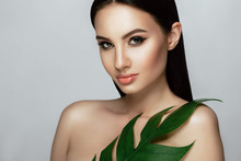 Beautiful Woman Face With Perfect Makeup And Healthy Skin With Tropical Leaf. Beauty Face Care