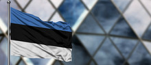 Estonia Flag Waving In The Wind Against Blurred Modern Building. Business Concept. National Cooperation Theme.