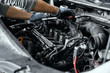 Close up of man's hands using wrench to remove spark plugs