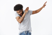 Swag In Air. Portrait Of Handsome And Stylish Cool African American Party Guy With Beard And Tattoos Sweep Hand Right And Looking Down As Making Dance Move, Shaking And Having Fun Over Gray Wall