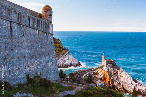 Fototapeta The walls of the Doria Castle in Porto Venere, La Spezia, Italy, overlooking the Gulf of Poets and the spectacular Church of Saint Peter (Chiesa di San Pietro) surrounded by turquoise waters