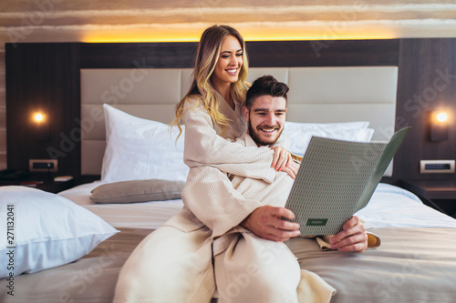 Fotografia, Obraz Couple in hotel room reading room service menu together in bed