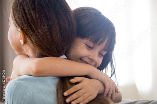 Cuadros en Lienzo Cute little girl hug young mom showing love and care