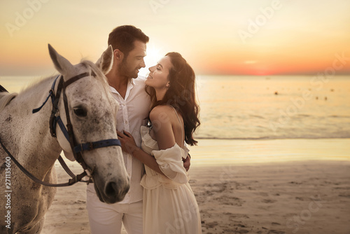 Tuinposter Artist KB Young couple walking a majestic horse - seaside landscape